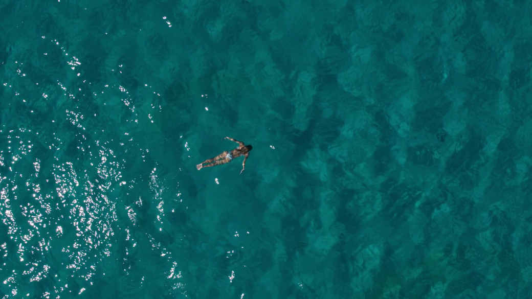 aerial-top-down-view-of-a-woman-swimming-underwater-in-a-deeper-water-with-white-sand-making-the-color-of-water-darker_sxfvpdmeex_thumbnail-full06.png